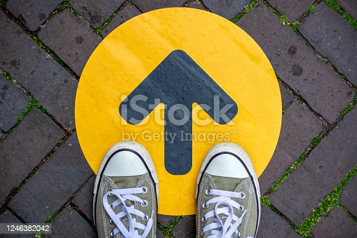 Feet wearing sneakers in front of arrow on road outdoors. Direction arrow in front of a store for the social distancing during the covid-19 pandemic.