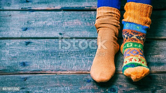 Female feet wearing odd wool socks on the wooden floor. Closeup view