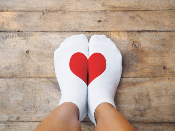 feet wearing white socks with red heart shape stock photo