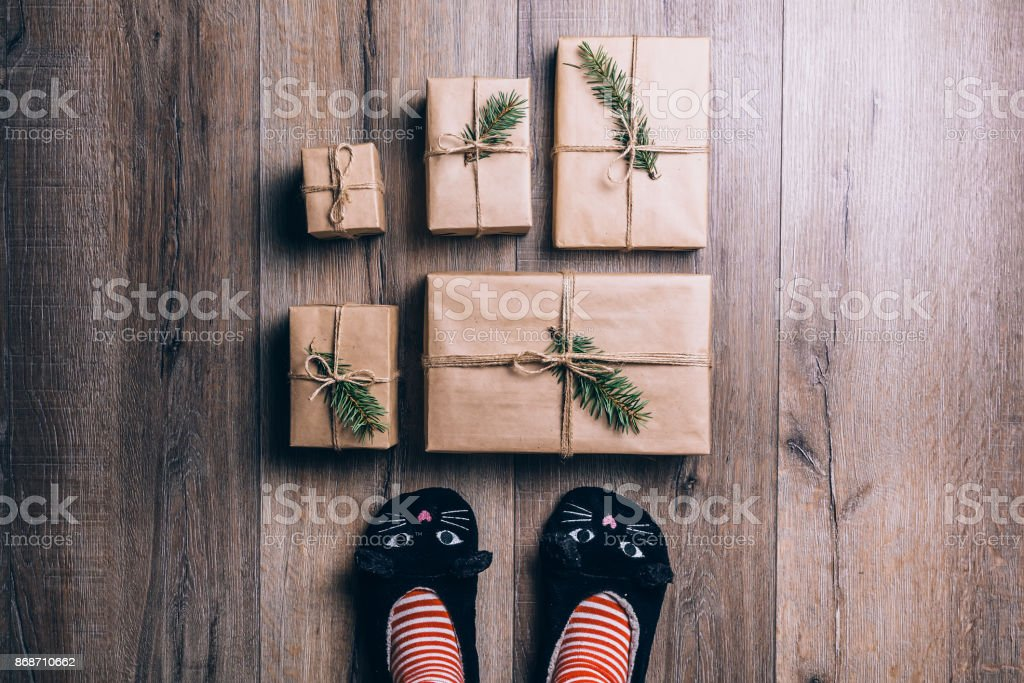 Feet with warm winter socks and cat slippers standing in front of Christmas gifts. top view stock photo