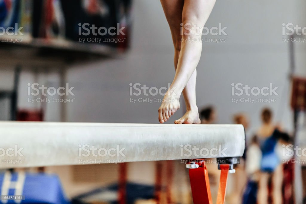 feet woman gymnast exercises on balance beam competition in artistic gymnastics stock photo