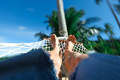 Feets in a hammock on a summer tropical nature background vacation concept