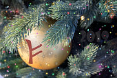 Fehu rune on background of Christmas tree