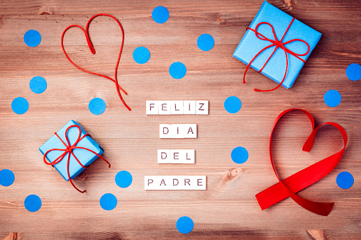 Feliz dia del padre words made of wooden blocks with blue gift boxes and red hearts on wooden background. Happy fathers day greeting card, holiday flat lay, top view