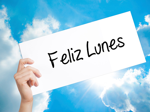 Feliz Lunes (Happy Monday In Spanish) Sign on white paper. Man Hand Holding Paper with text. Isolated on sky background