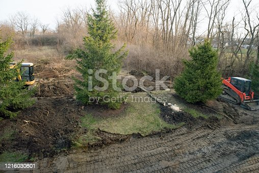 Aerial view of land being excavated with felling of deciduous trees.