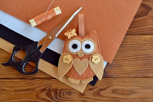 Felt brown owl embellishment. Kids easy art. Toy with wooden buttons. Scissors, thread, needles, felt pieces. Kit for sewing bird toy. Shabby chic. Brown wooden table. Easy Christmas ornaments to make diy holiday crafts. Easy Christmas ornaments kids. Handcraft ideas diy handmade gifts. Handmade decorations for home diy projects. Handmade home decor crafts diy projects