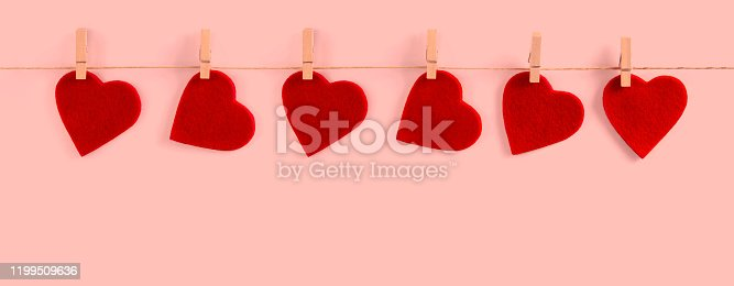 Valentine background with red felt hearts row border on clothespins on white background
