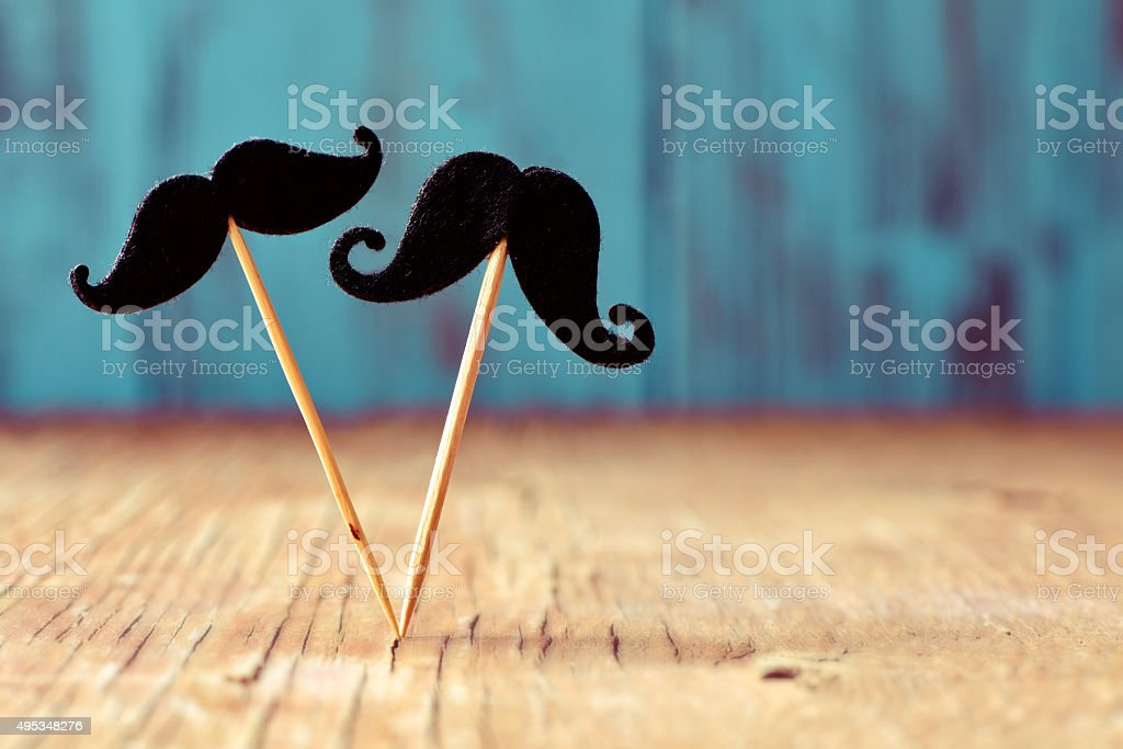 felt mustaches in sticks on a wooden surface stock photo