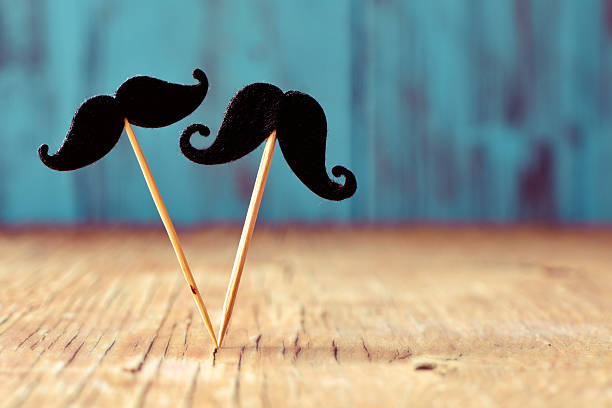 felt mustaches in sticks on a wooden surface - mustache stock pictures, royalty-free photos & images