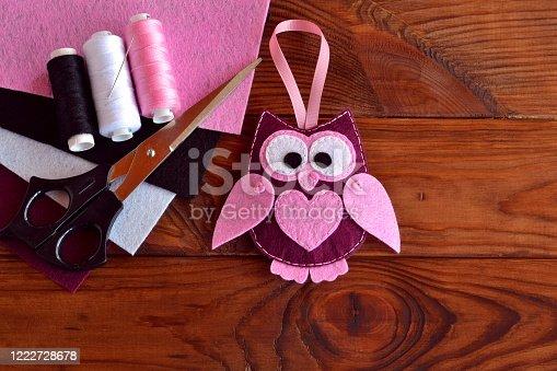 istock Felt owl embellishment. Felt owl toy. Kids DIY crafts. Sheets of colored felt, scissors, thread, needle, wooden table 1222728678
