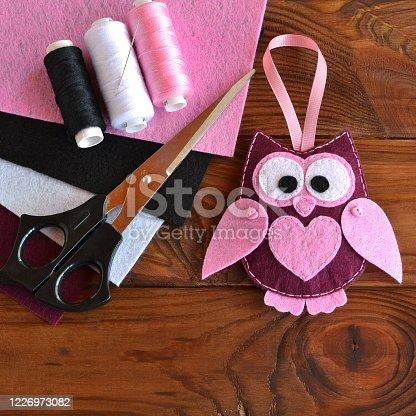 istock Felt owl toy. Kids DIY crafts. Sheets of colored felt, scissors, thread, needle, wooden table 1226973082