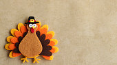 Orange brown and yellow felt turkey with pilgrim hat on a tan background with writing space