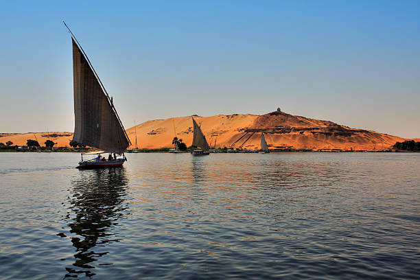 Felucca boats sailing across a lake in the late afternoon stock photo