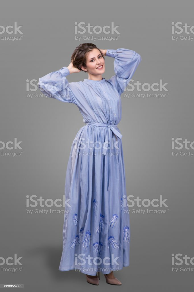 femail model wear long blue dress over gray background. stock photo