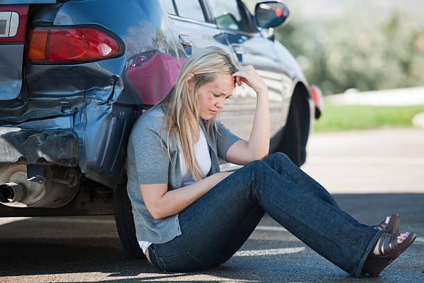 femal accident victim waits outside of her car - head injury stock photos and pictures