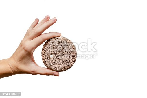 istock Femal hand holding pumicestone. Skin care Concept. White background, isolated, close up 1249910718