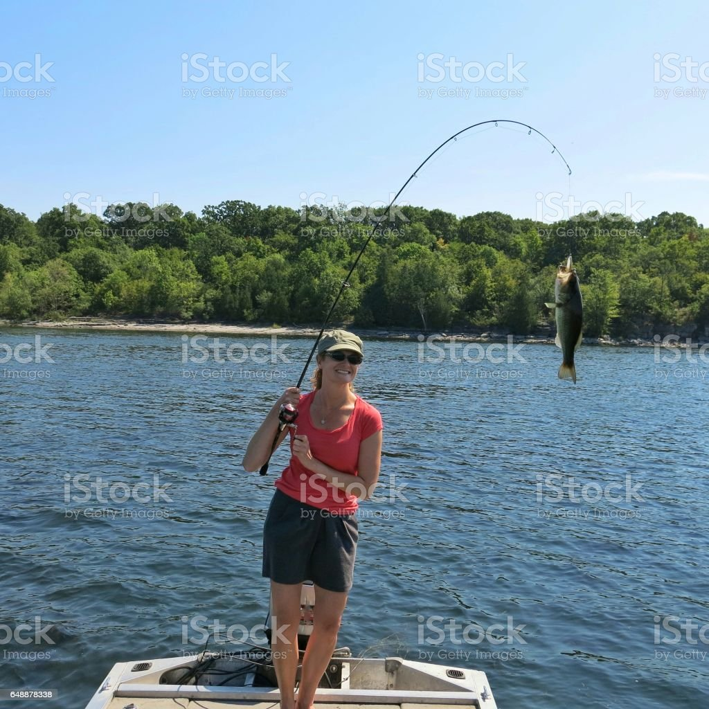 Female 30s Fishing Catching Smallmouth Bass, Boat, Lake Champlain, NY stock photo
