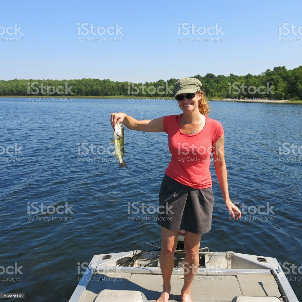 Female 30s Fishing Holding Smallmouth Bass, Boat, Lake Champlain, NY stock photo