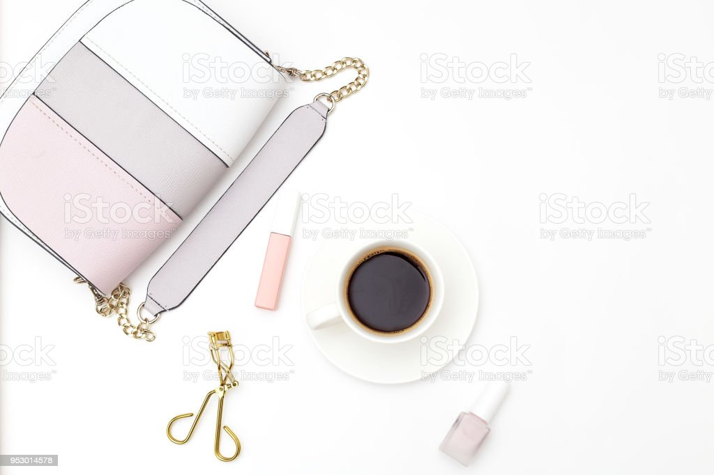 Female accessories and a cup of coffee on a white background. Copy space stock photo