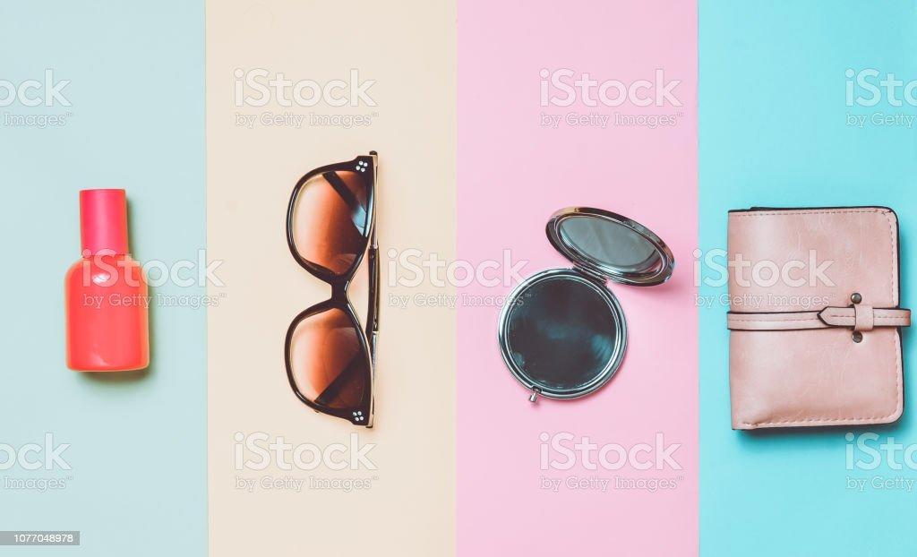 116d5755ca3e acessórios femininos em um fundo colorido. Óculos de sol, frasco de perfume,  espelho