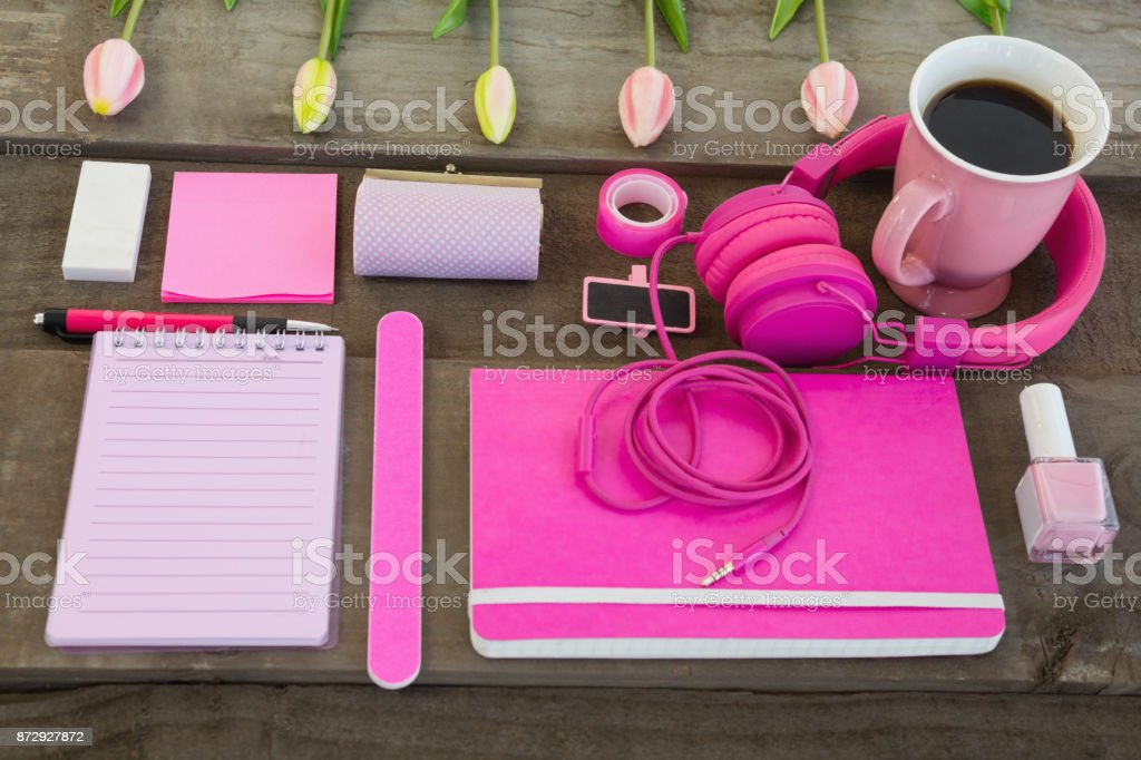 Female accessories, stationery and coffee on wooden surface stock photo