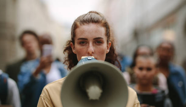 Female activist protesting with megaphone during a strike stock photo
