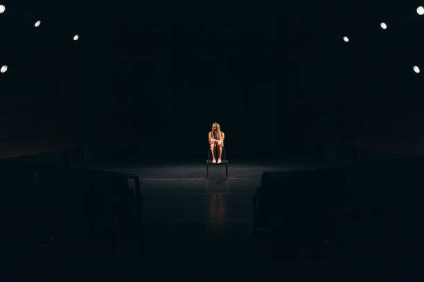 female actress alone on stage stock photo