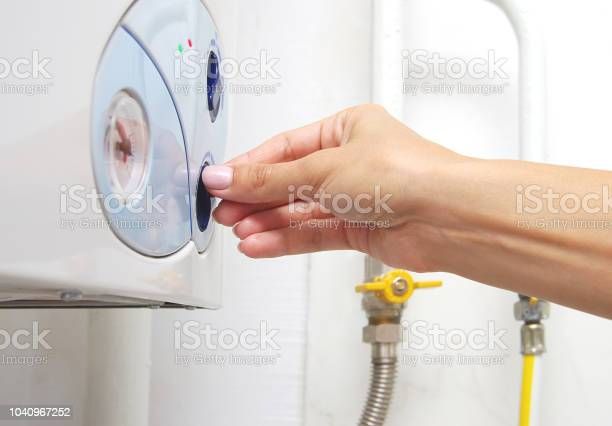 Photo of Female adjusting a central heating gas boiler at home.
