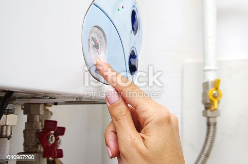 996279800istockphoto Female adjusting a central heating gas boiler at home. 1040967260