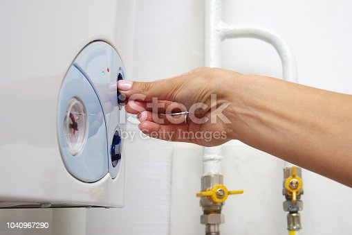 996279800istockphoto Female adjusting a central heating gas boiler at home. 1040967290