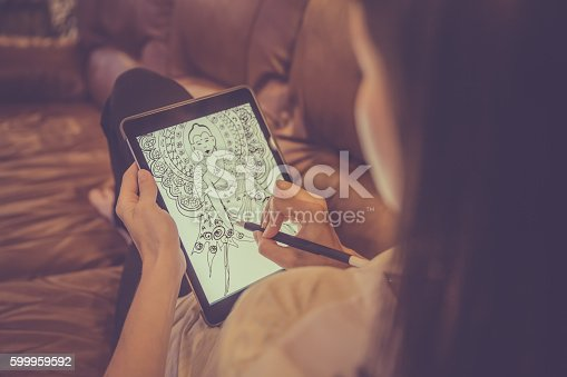 DSLR picture of Female Hands Drawing Mandala on Electronic Tablet.