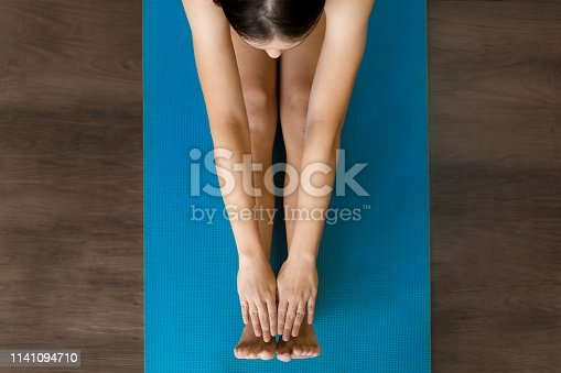 914755474 istock photo Female adult stretching on a yoga mat in class. 1141094710