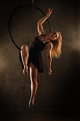 Female aerial dancer in black dress. Young sports girl dancing with an air hoop. She is dressed in a black dress.