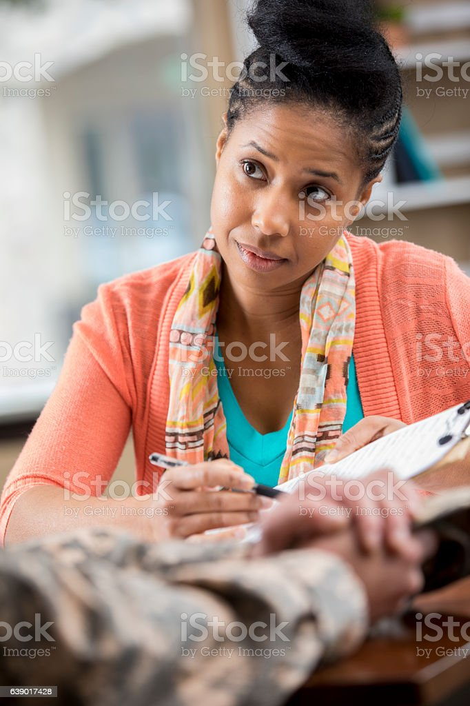 Female African American counselor talks with unrecognizable soldier stock photo