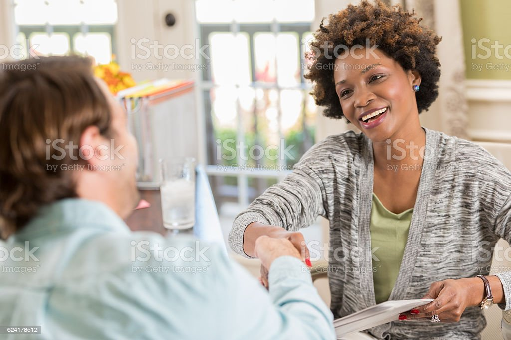 Female African American entrepreneur greets client in home office stock photo
