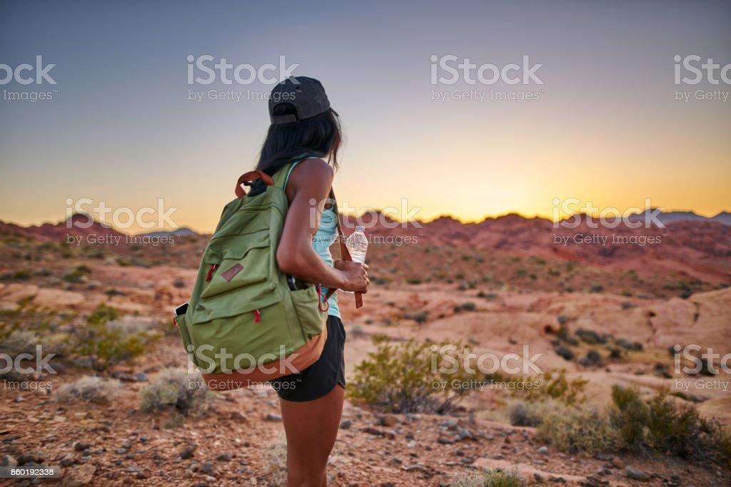 female african american hiker watching sunset in nevada desert stock photo