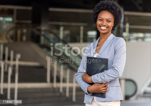 istock Female African American job seeker keeping a folder with CV 1165677303