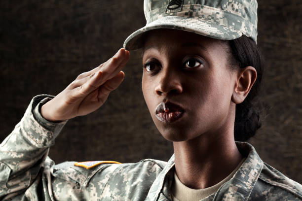 female african american soldier series: against dark brown background - saluting stock photos and pictures