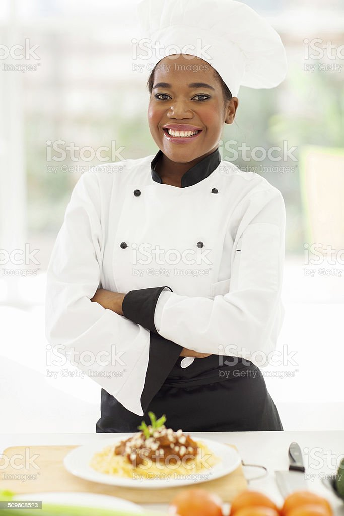 female african chef with arms crossed stock photo