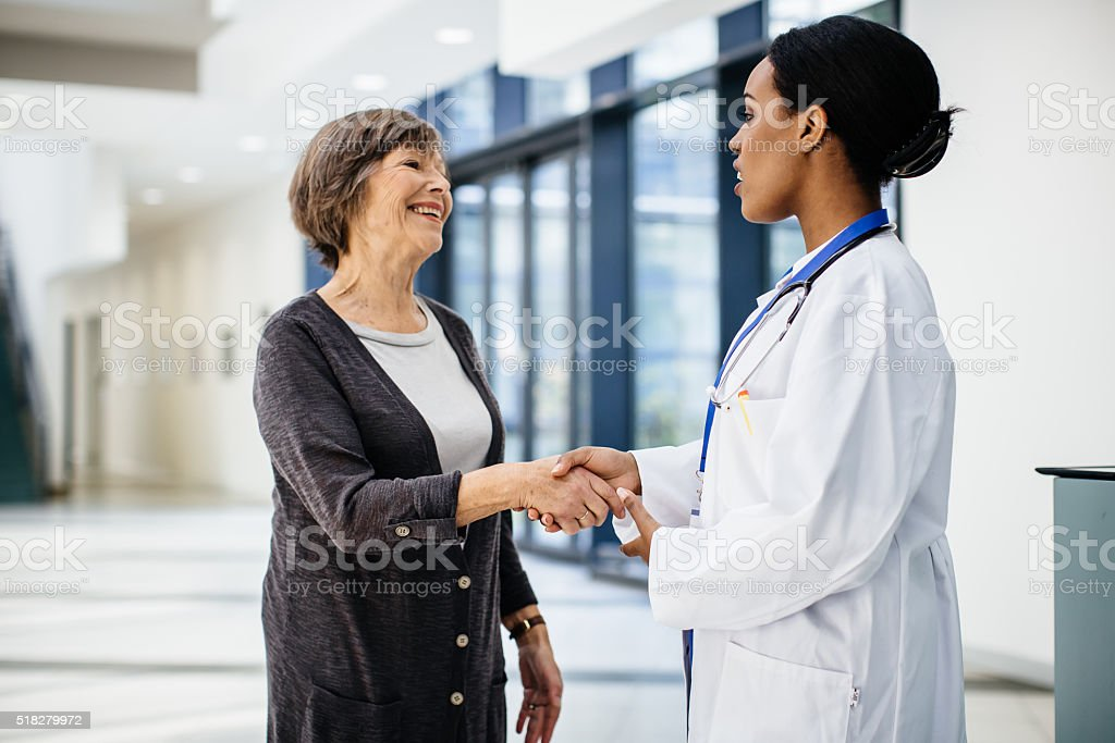 Female african doctor welcomes senior patient stock photo