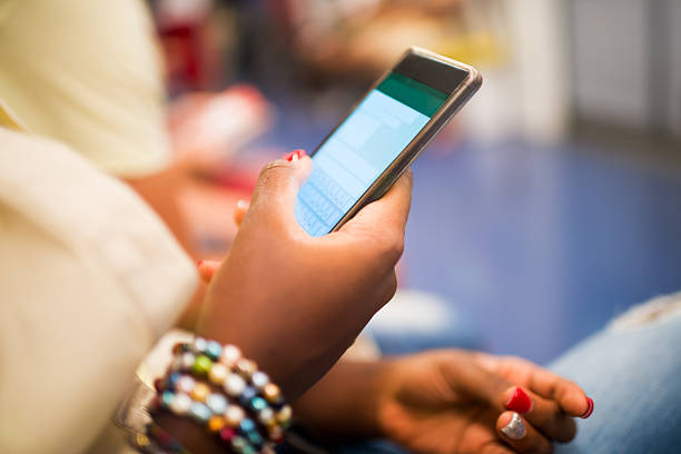 Female african hands holding mobile phone stock photo