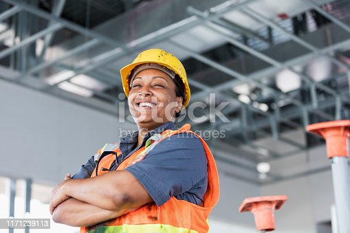 A mature African-American woman in her 40s wearing a hardhat and reflective vest, a construction worker or building contractor, standing with her arms crossed, smiling at the camera.