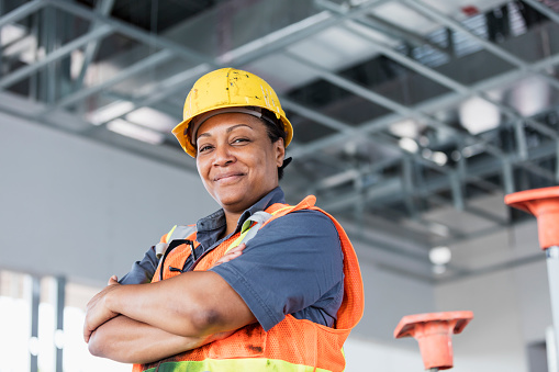A mature African-American woman in her 40s wearing a hardhat and reflective vest, a construction worker or building contractor standing with her arms crossed, smiling at the camera.