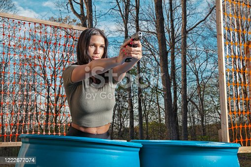 Female in her 30's at a shooting range with pistol aiming at target.