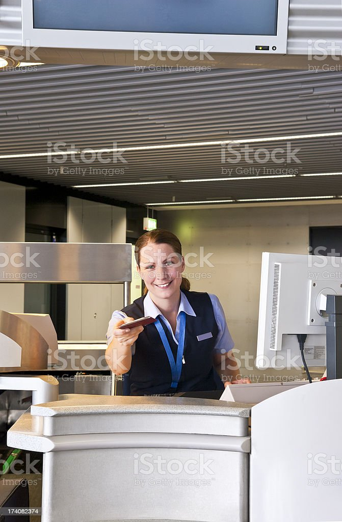 Female airline employee handing tickets stock photo