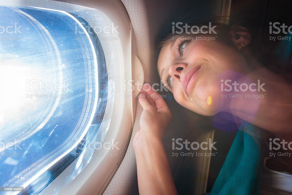 Female airplane passenger enjoying view from the window stock photo