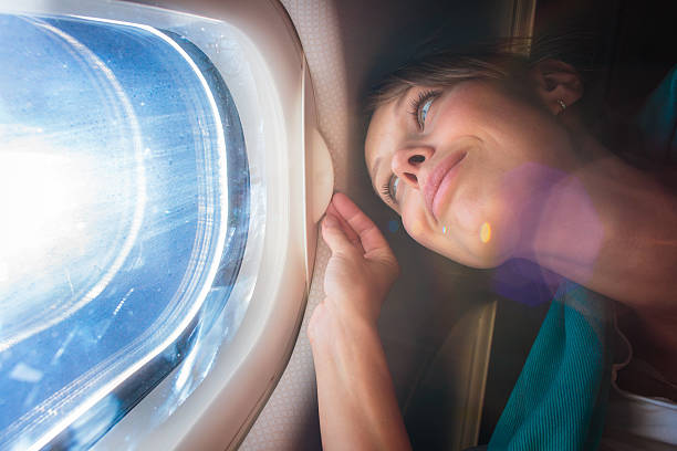Female airplane passenger enjoying view from the window stock photo