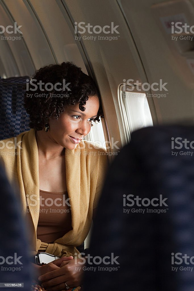 Female airplane passenger looking out of window royalty-free stock photo