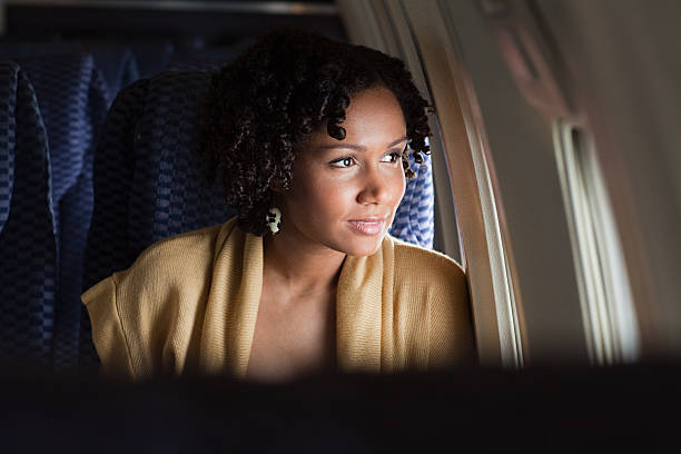 Female airplane passenger looking out of window stock photo